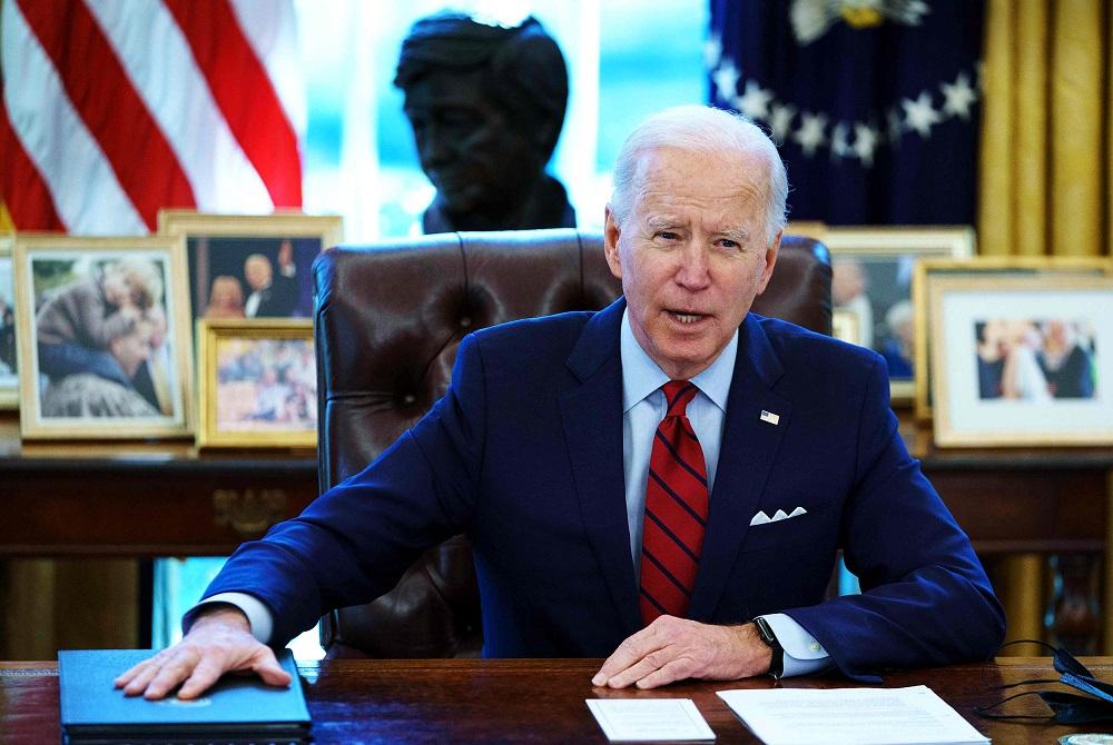Joe Biden amerikai elnök egy íróasztal mögött ülve