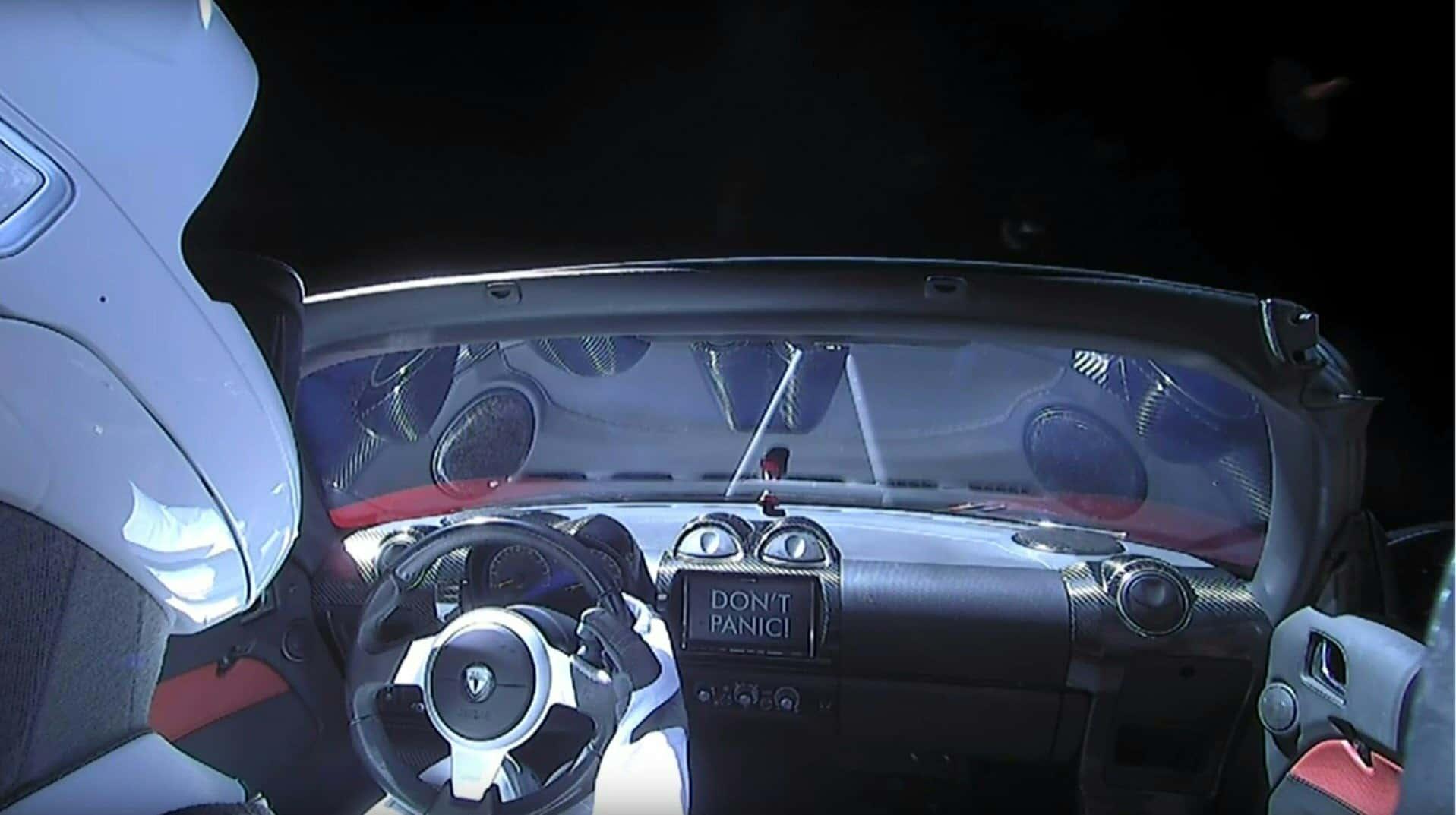 """Starman a Tesla Roadster volájnánál, a kijelzőn a """"DON'T PANIC!"""" felirat"""