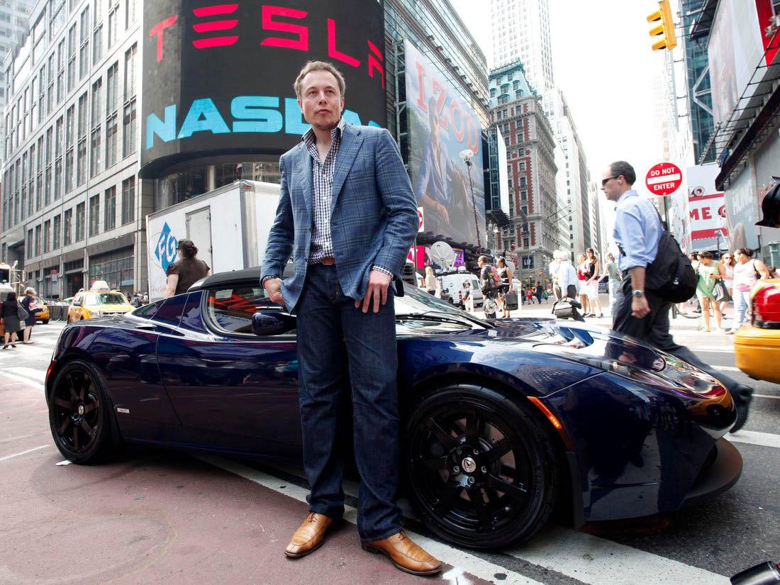 Elon Musk egy Tesla Roadster előtt a Wall Streeten